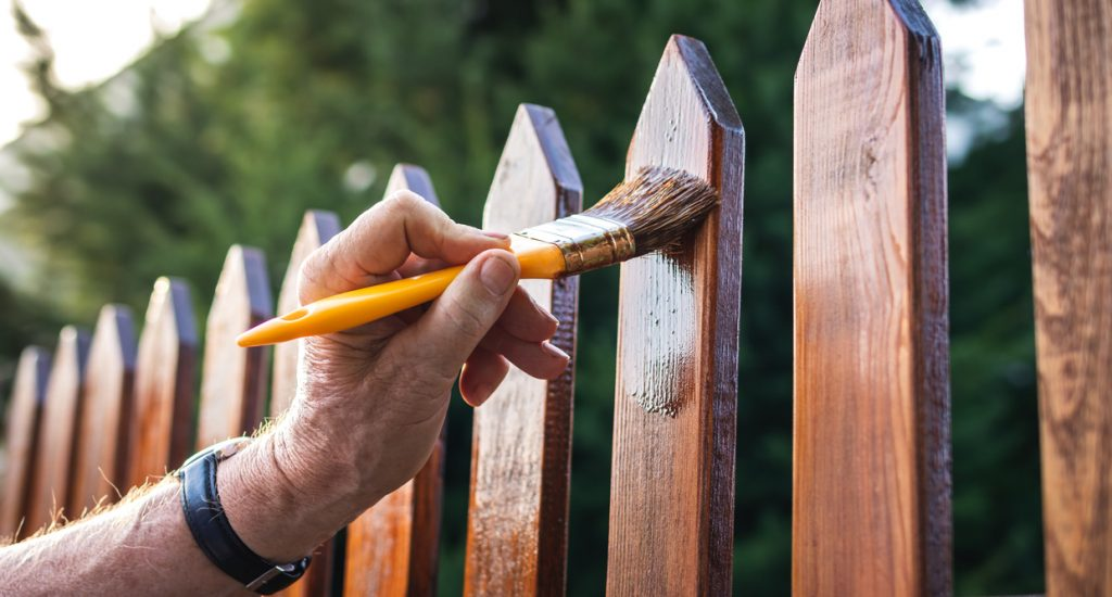 Close-up hand with paintbrush painting wooden picket fence outdoors